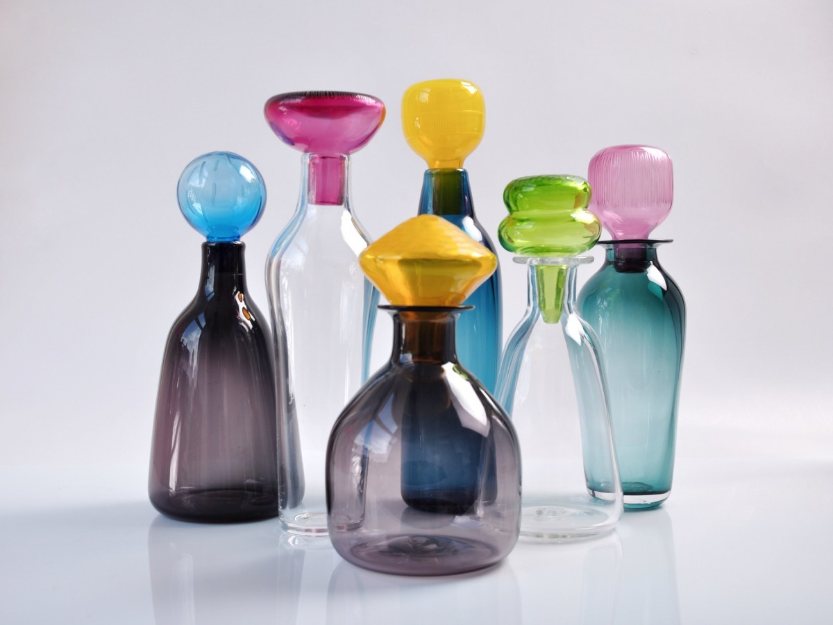 Group of six glass bottles with multi-coloured stoppers