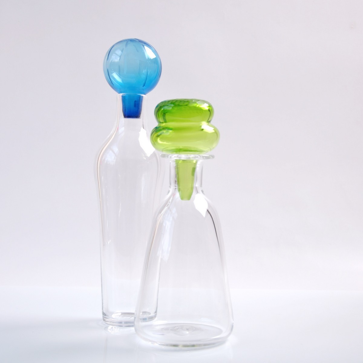 Two clear glass bottles with coloured stoppers