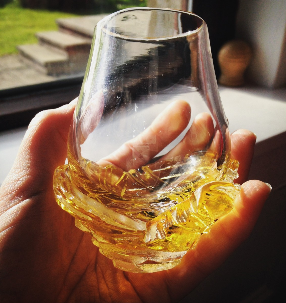 Hand holding a whisky glass with a carved amber base