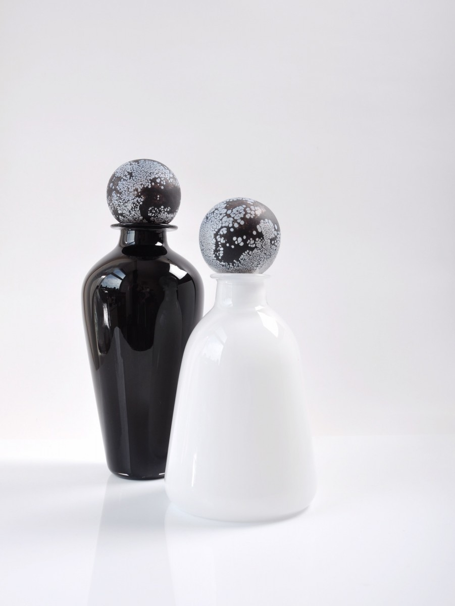 One black and one white bottle with patterned black and white stoppers