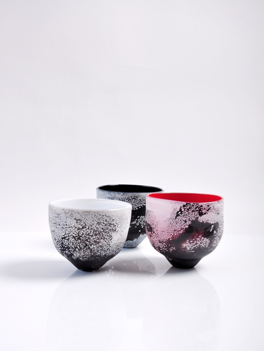 Three glass tea bowls with black and white patterned exteriors and red, white and black interiors