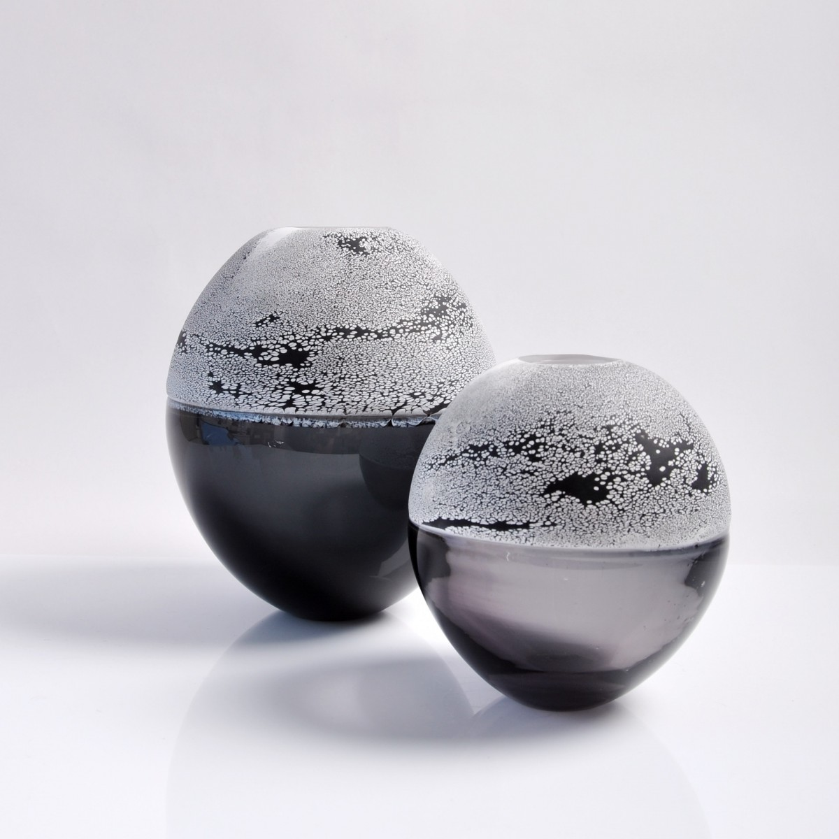 Two glass vases with grey bottom halves and black and white patterned top halves