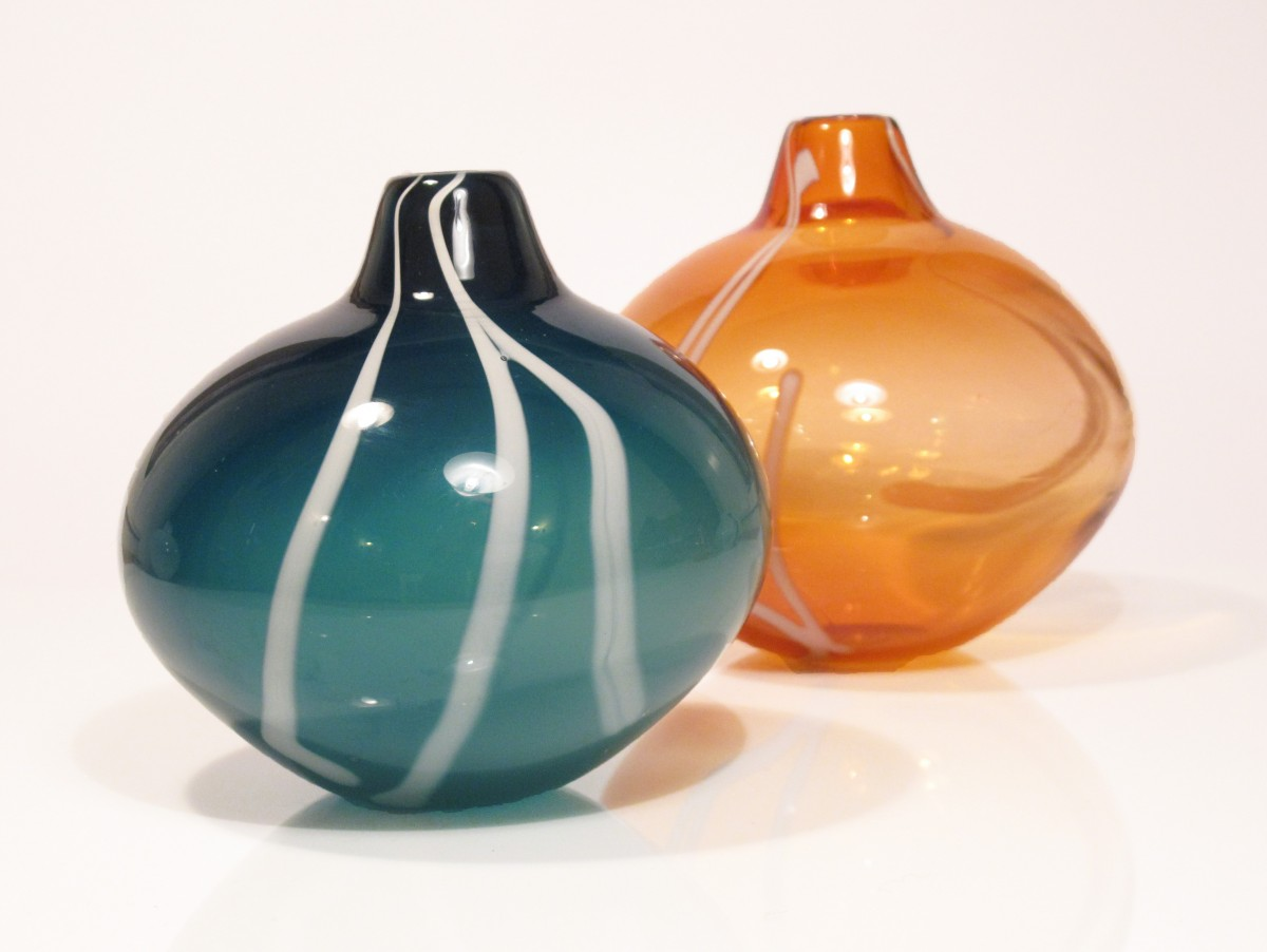Two glass vases, one sea green and one apricot with white stripe pattern