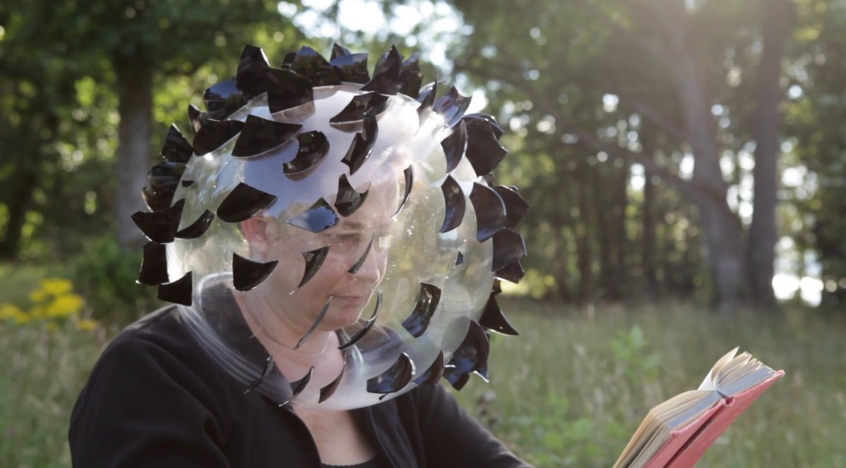 Still from a video showing the artist reading a book whilst wearing a clear glass dome over her head, covered in black glass shards.