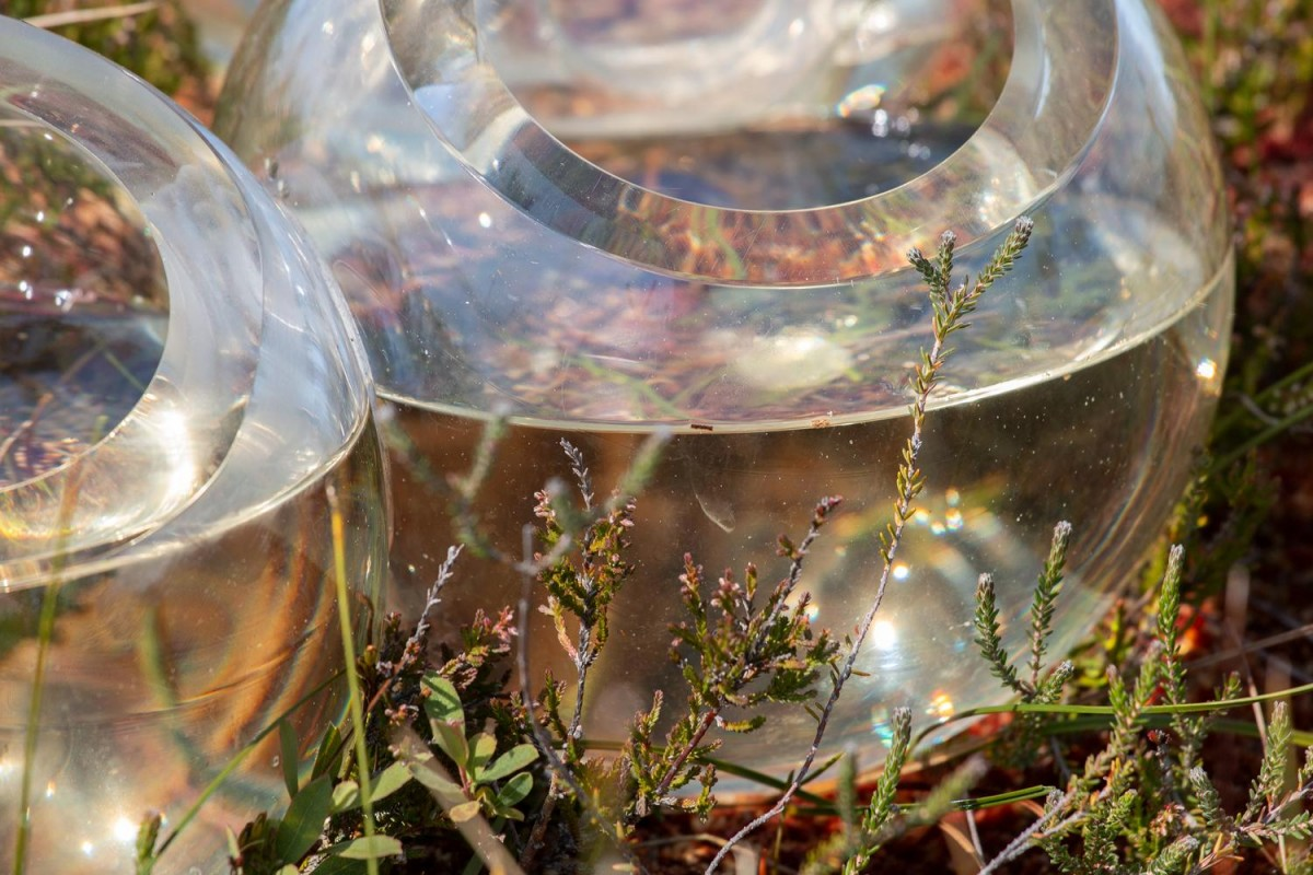 Close up of clear glass bubbles containing water, sitting in the landscape