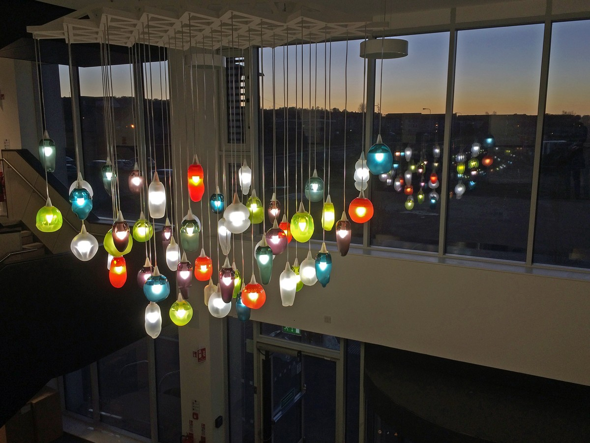 A group of brightly coloured glass lights hang from the ceiling and are reflected in the windows of the building.