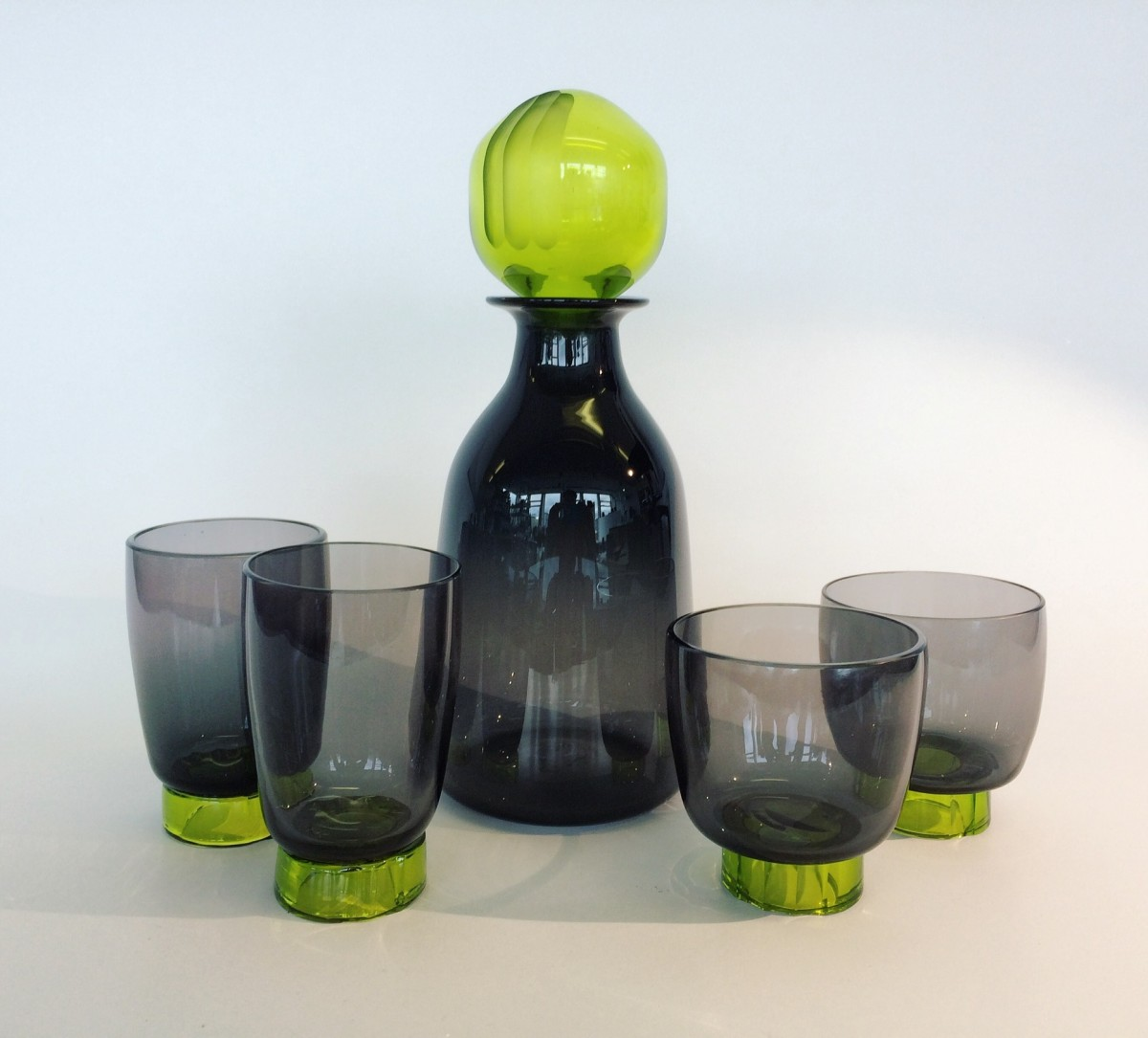 Grey glass decanter and four glasses with lime green stopper and feet