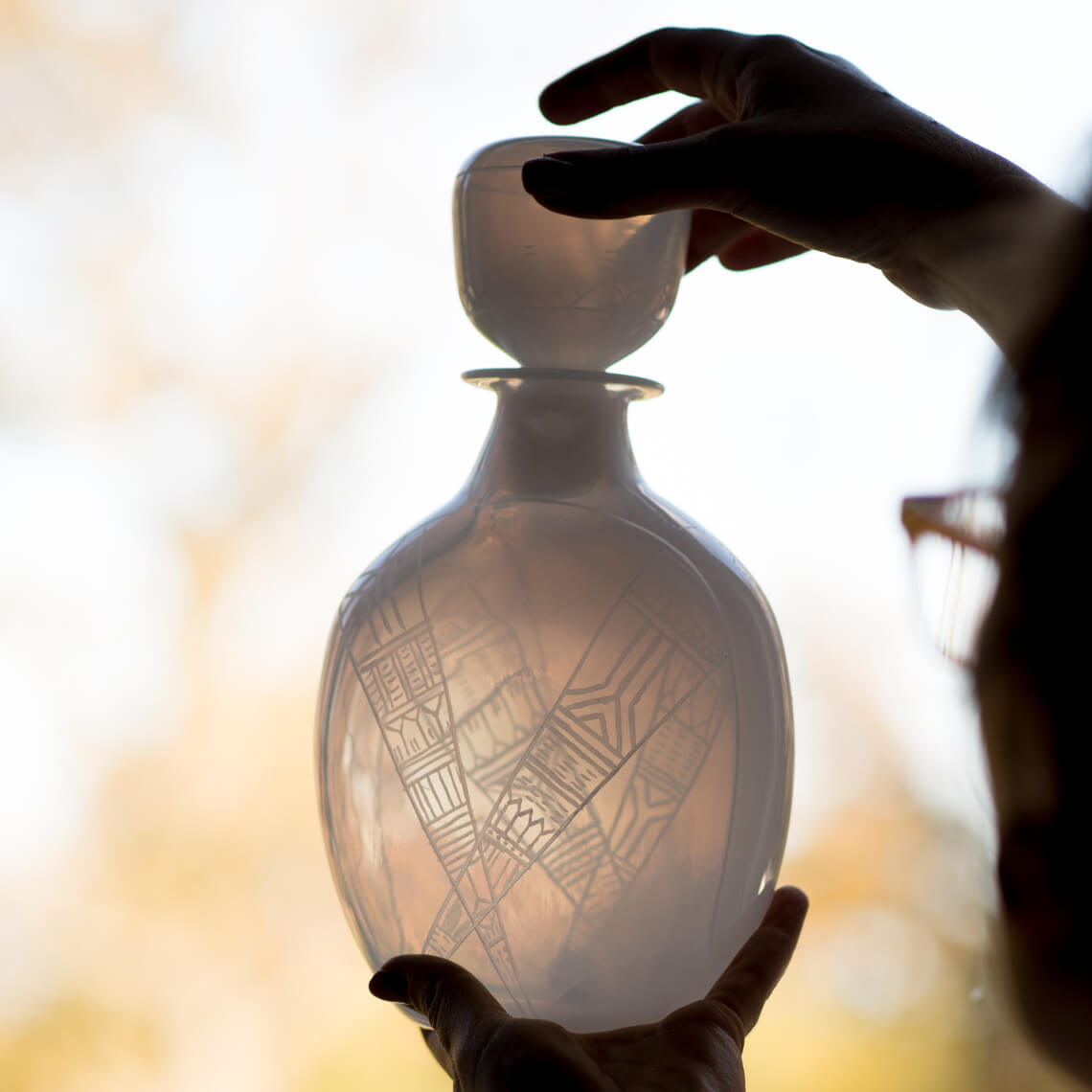 Translucent white decanter being held up to the light. Geometric patterns are engraved on its surface